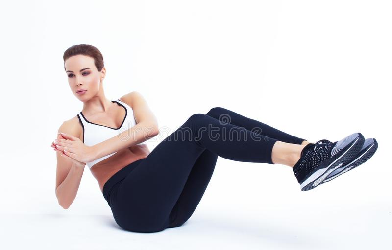 Young fit woman doing russian twist exercise. Young fit woman doing russian twist, abs exercise stock image