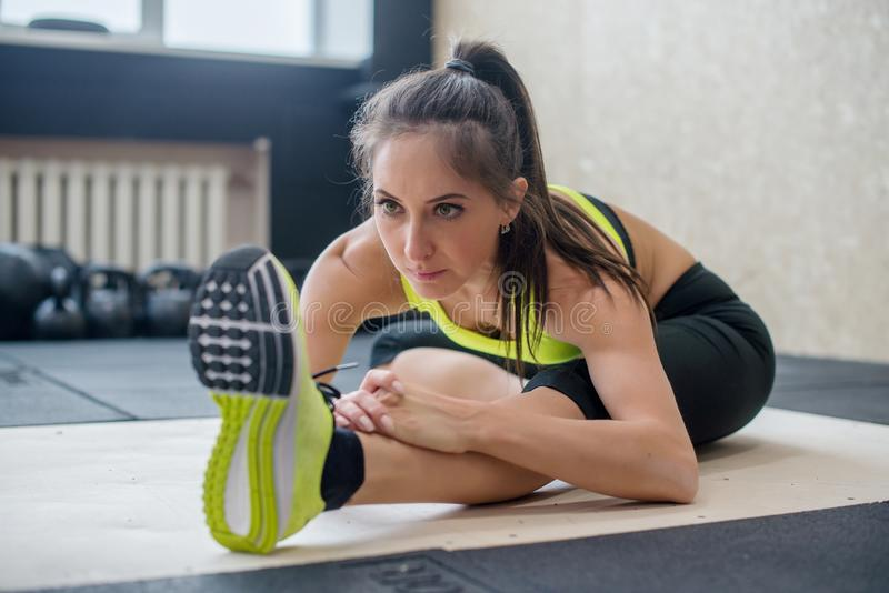 Young fit woman doing seated forward fold exercise, sporty female stretching royalty free stock image