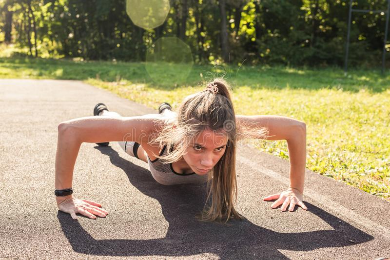 Young fit woman exercising by doing push-ups outdoors.  stock photos