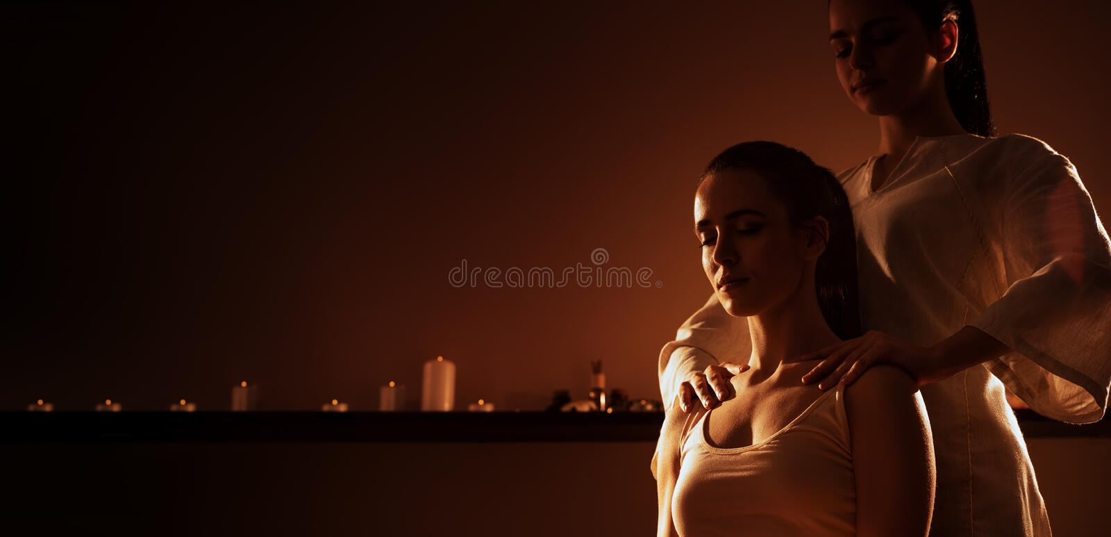 Young fit woman has Thai massage at luxury spa. Warm inviting colors, calm atmosphere, charming light. Copy space. Young fit women has Thai massage at luxury spa royalty free stock photos