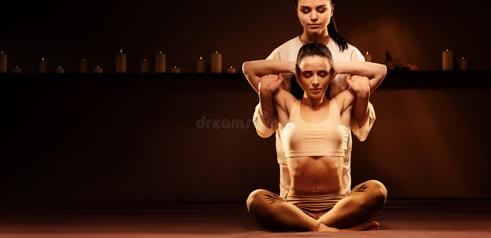 Young fit woman has Thai massage at luxury spa. Warm inviting colors, calm atmosphere, charming light. Copy space. Young fit women has Thai massage at luxury spa stock photography