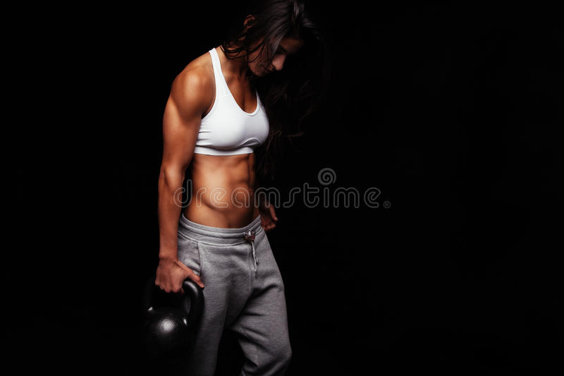 Young fit woman holding kettle bell. Exercising against black background. Muscular female doing crossfit exercise stock image