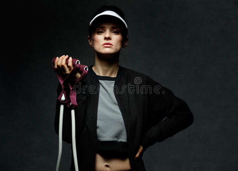 Young fit woman holding resistance band against dark background stock photo