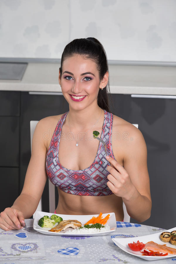 Young fit woman in the kitchen, eating royalty free stock images