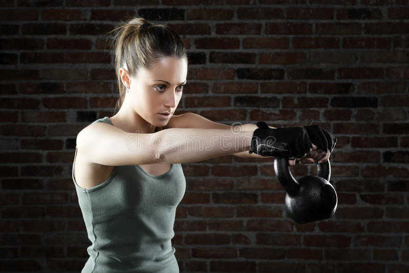Young fit woman lifting kettle bell. Portrait of Young fit woman lifting kettle bell stock image