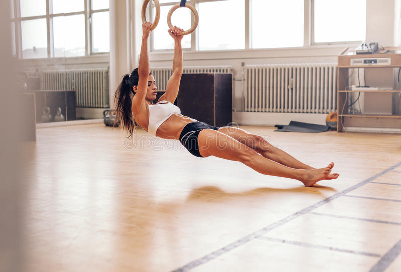 Young fit woman pulling up on gymnastic rings stock photography