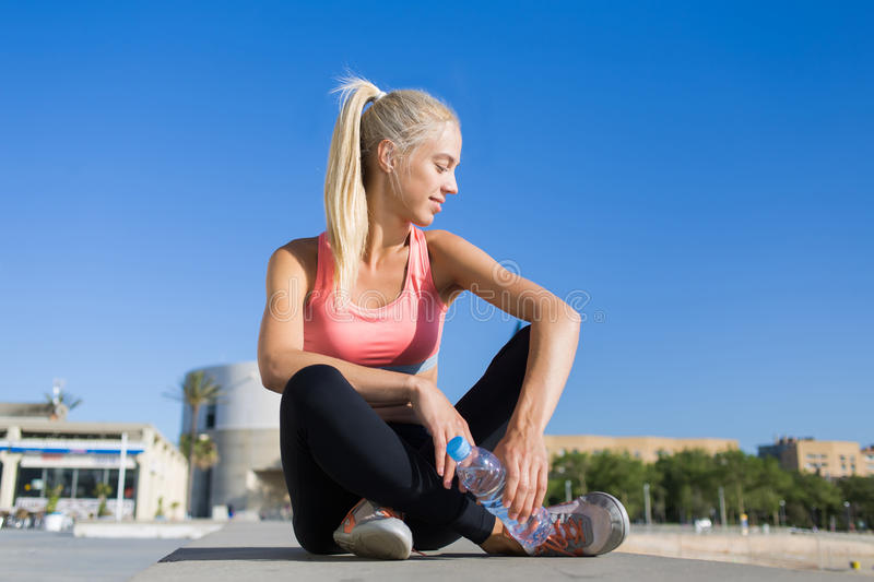 Young fit woman in sportswear taking break after run royalty free stock image