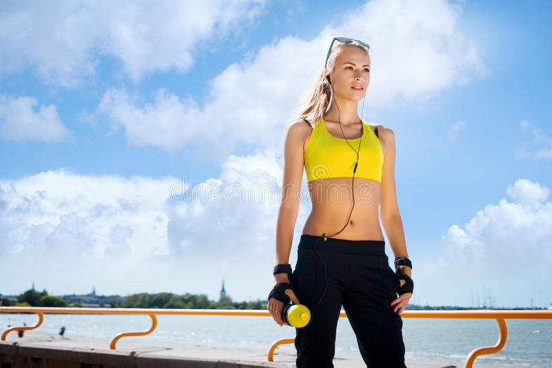 Young and fit woman in sporty clothes training outdoors stock photos