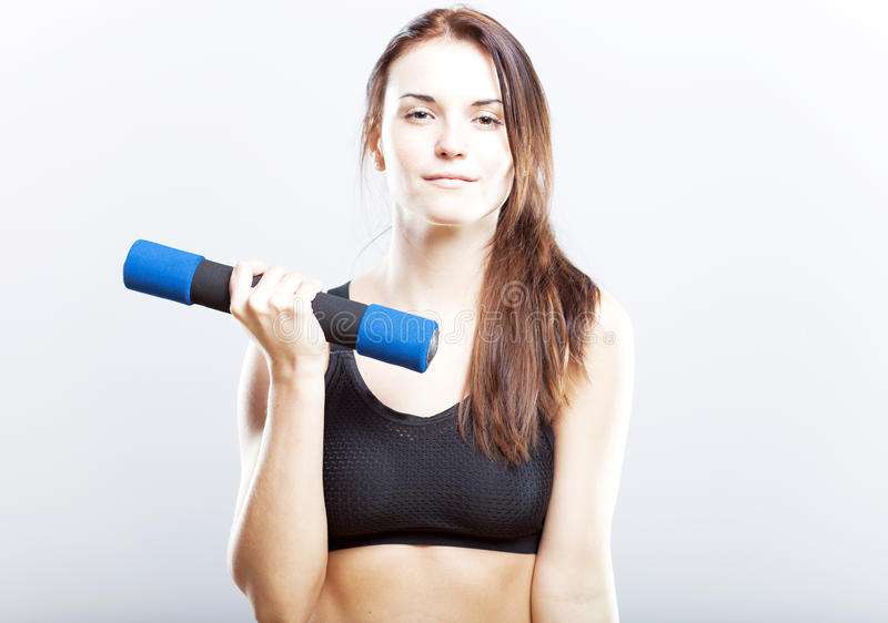 Young fit woman training with dumbbells royalty free stock photography