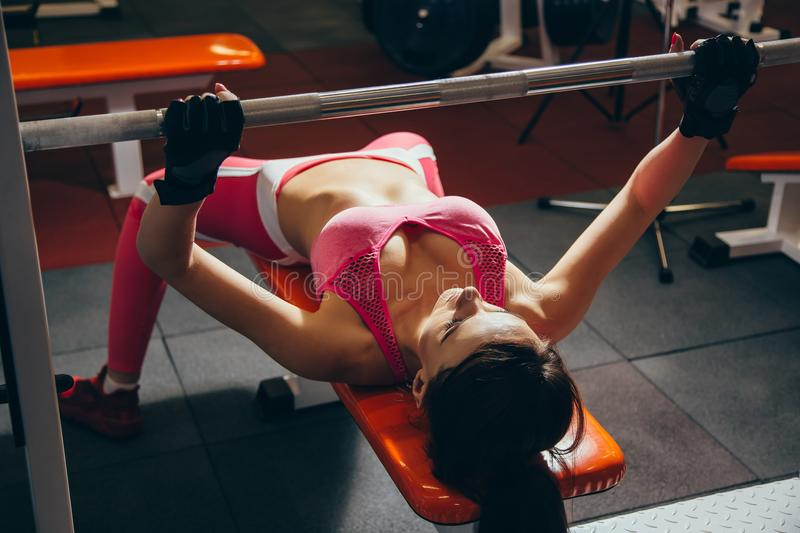 Young fit woman working out with barbell on bench in the gym. Bar Bench Pres royalty free stock photography