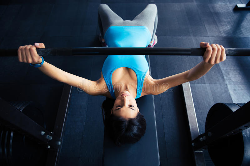 Young fit woman working out with barbell on bench royalty free stock image
