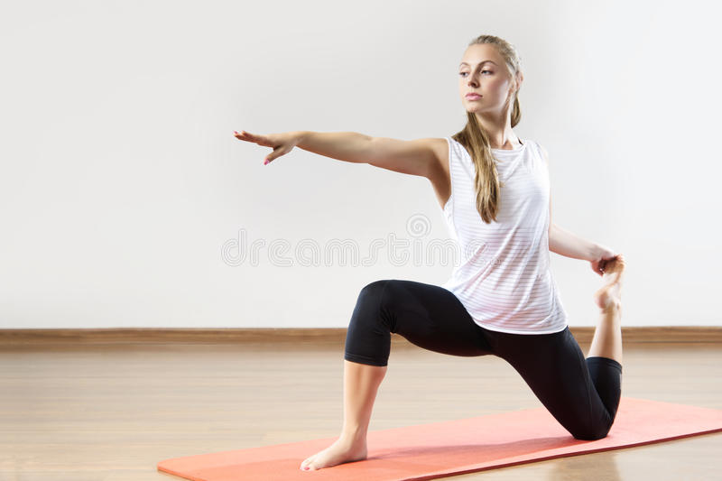 Young fit woman works out in the fitness class. Yoga asana. Space for placing text royalty free stock image