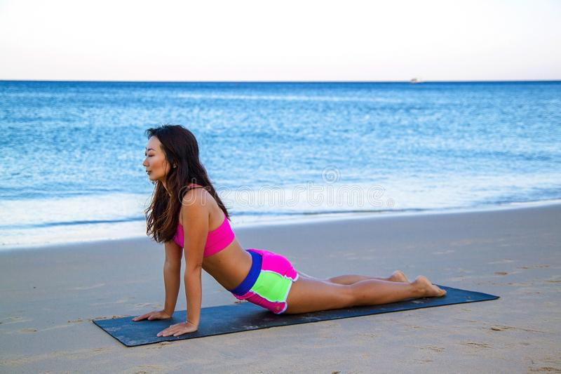 Young fitness asian woman on the beach doing core exercises royalty free stock photography