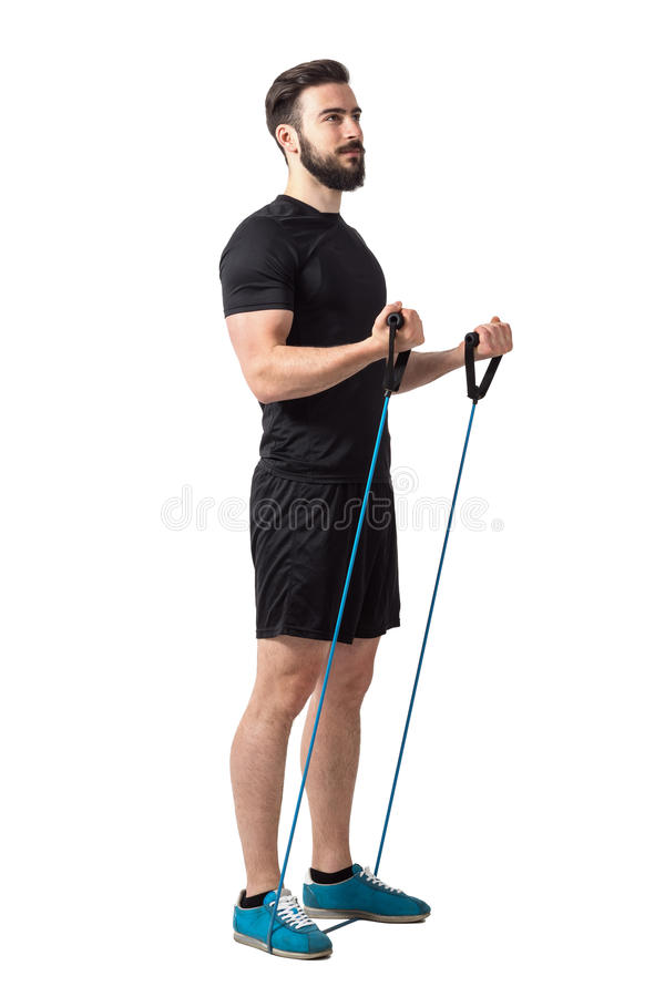Young fitness athlete doing bicep curl arms exercise with resistance bands. Full body length isolated over white studio background stock photography