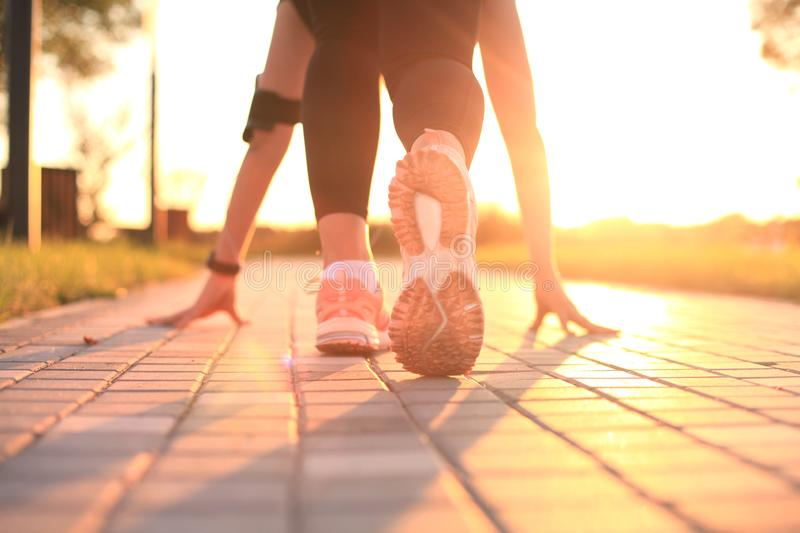 Young fitness attractive sporty girl runner in start position, closeup on shoe, outdoor at sunset or sunrise. Young fitness attractive sporty girl runner in stock images