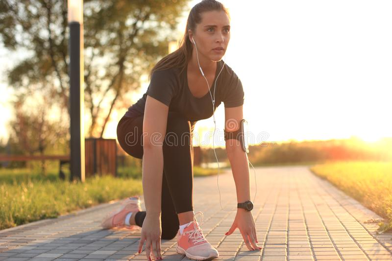 Young fitness attractive sporty girl runner in start position outdoor at sunset or sunrise. Young fitness attractive sporty girl runner in start position stock photography