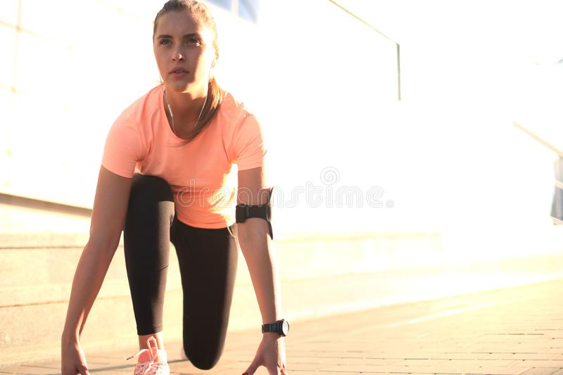 Young fitness attractive sporty girl runner in start position outdoor at sunset or sunrise in city. Young fitness attractive sporty girl runner in start stock photos