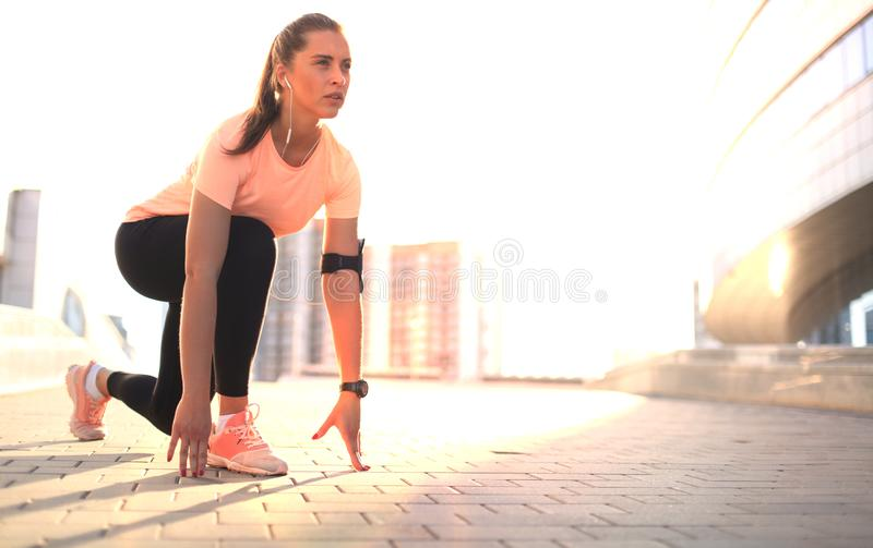 Young fitness attractive sporty girl runner in start position outdoor at sunset or sunrise in city. Young fitness attractive sporty girl runner in start stock image