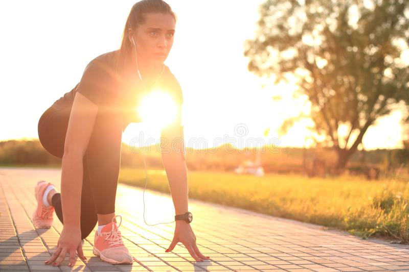 Young fitness attractive sporty girl runner in start position outdoor at sunset or sunrise. Young fitness attractive sporty girl runner in start position stock photos