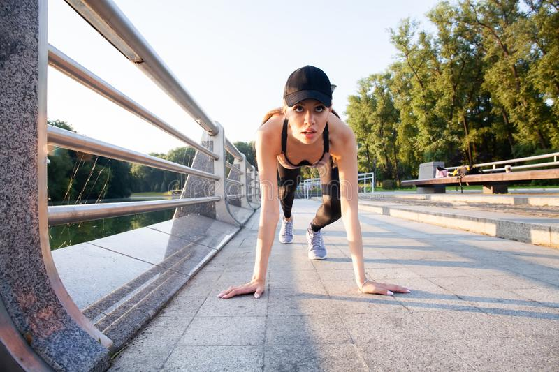 Young fitness attractive sporty girl runner in start position outdoor at sunset or sunrise. Young fitness attractive sporty girl runner in start position royalty free stock photos