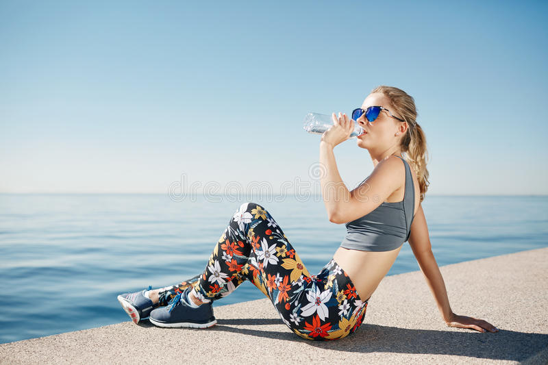 Young fitness blonde woman drinking water after running at beach royalty free stock images