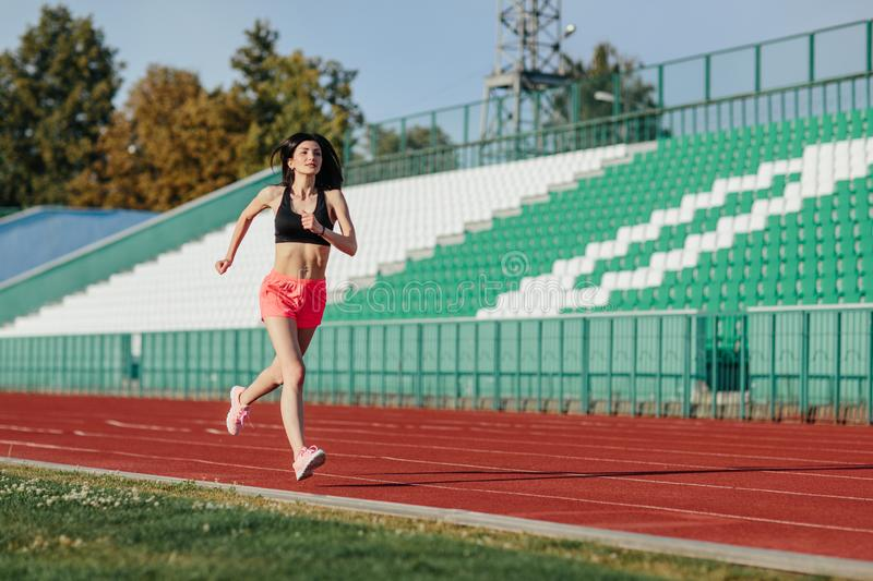 Young fitness brunette woman in shorts and top running on a stadium track. Athlete girl doing exercises on the training at stadium. Healthy active lifestyle royalty free stock photo