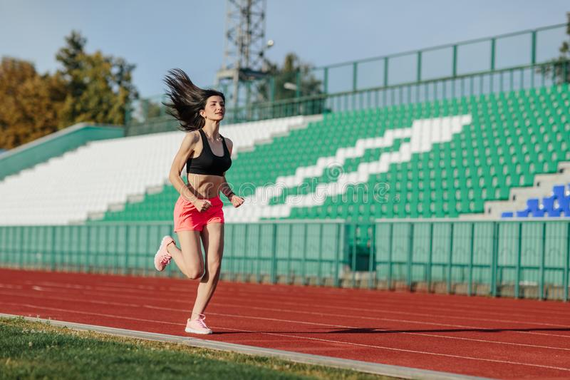 Young fitness brunette woman in shorts and top running on a stadium track. Athlete girl doing exercises on the training at stadium. Healthy active lifestyle stock image
