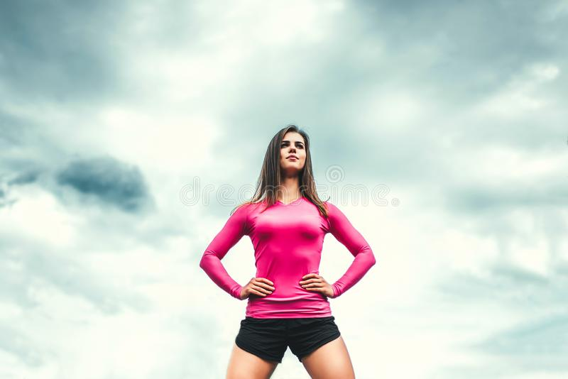 Young fitness coach girl with sky on background royalty free stock images