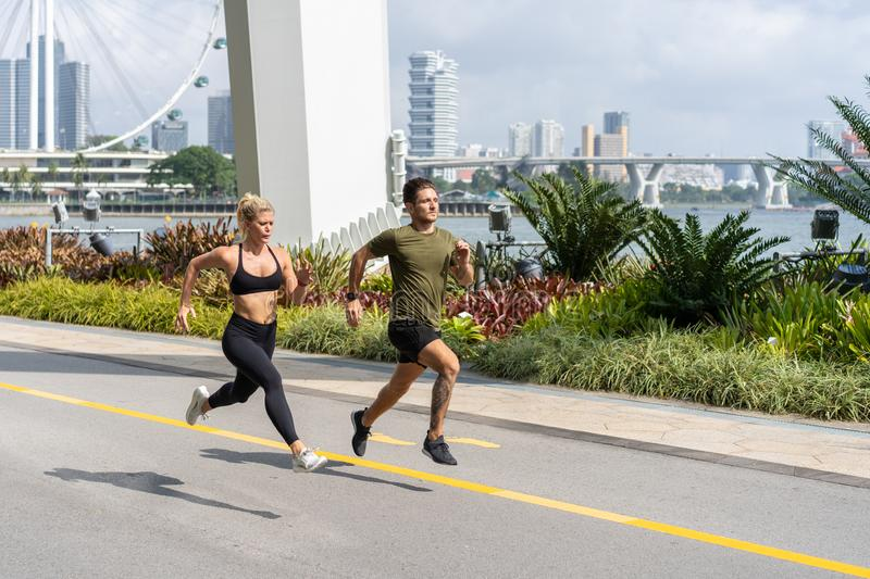 Young fitness couple running in urban area royalty free stock photography
