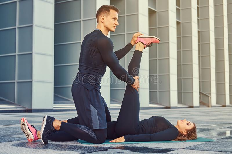 Young fitness couple in a sportswear, doing stretching while preparing for serious exercise in the modern city against a. Skyscraper royalty free stock photos