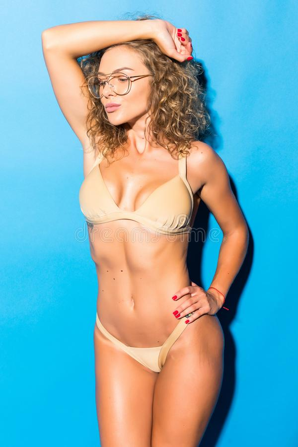 Young fitness curly girl in swimsuit is standing and flirting like model on the blue background royalty free stock images