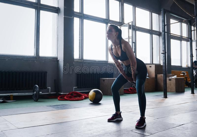 Young fitness female exercise with kettle bell. Caucasian woman doing crossfit workout at gym. royalty free stock image