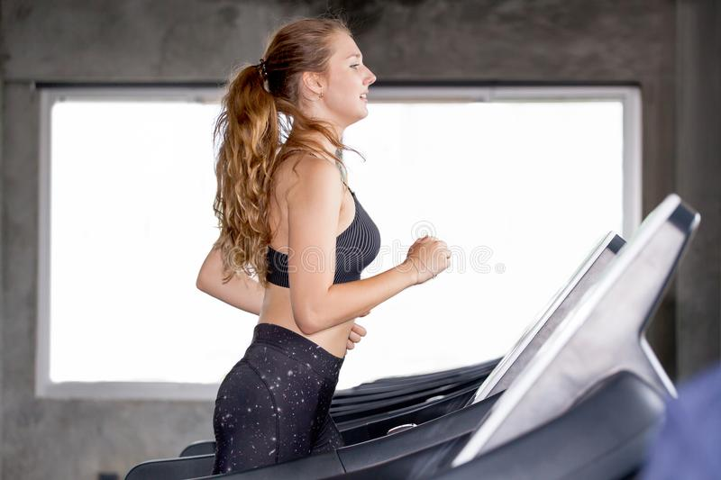 young fitness girl doing exercise running on treadmill in gym.woman in sportswear working out run on a machine healthy lifestyle royalty free stock image