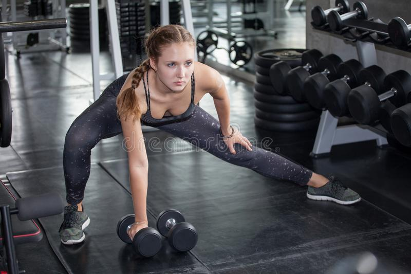 young fitness girl doing exercise squat with dumbbell in gym.woman in sportswear working out stretching royalty free stock photography
