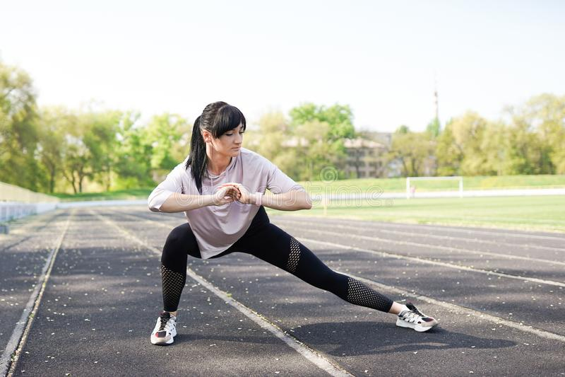 Young fitness girl doing stretching on the stadium. Summer sport activity. Green stadium background with copy space stock photos