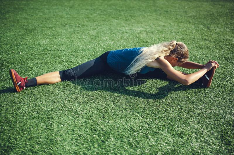 Young fitness girl doing stretching in the sunset . Football field. stock images