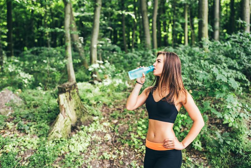 Young fitness girl drinking water in the park stock image
