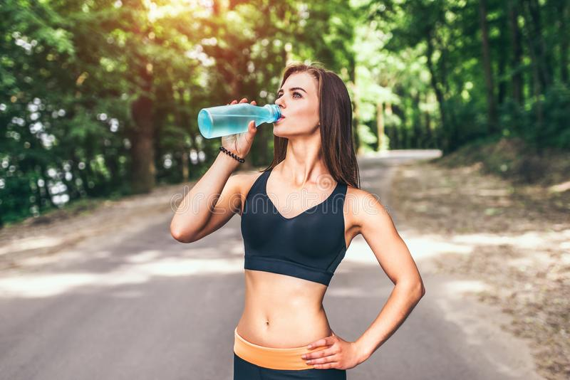 Young fitness girl drinking water in the park stock images