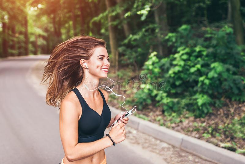 Young fitness girl running and listening music in the park royalty free stock images