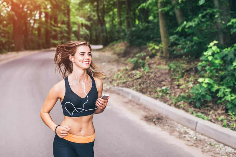 Young fitness girl running and listening music in the park stock image