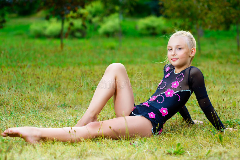 Young fitness girl sitting in park on green grass royalty free stock photos