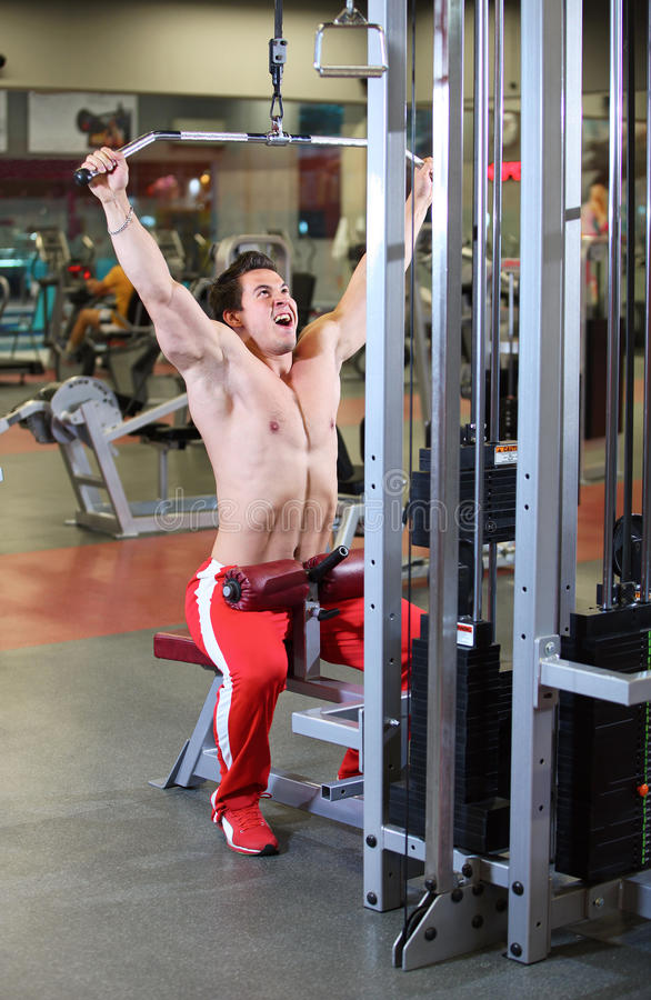 Young Fitness Guy Working Out On Exercise Machine Stock Photo