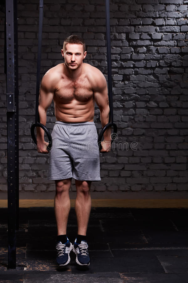 Young fitness handsome man doing dipping exercise using rings against brick wall in the cross fit gym. stock photos