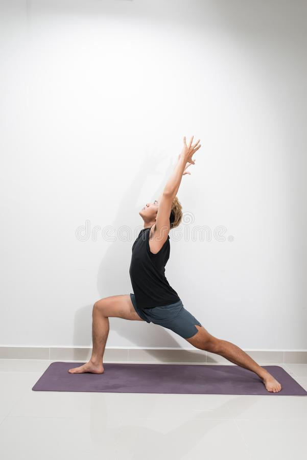 Young fitness man doing yoga exercise with Warrior 1 pose.  royalty free stock photography