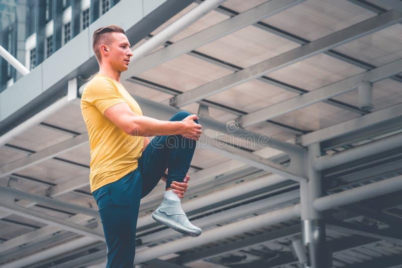 Fitness man runner stretching legs before run in a city. Young fitness man runner stretching legs before run in a city stock photography