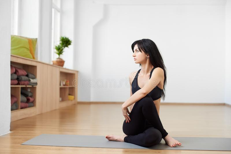 Young fitness model in black sportswear doing yoga, pilates training in modern yoga studio. Half lord of the fishes pose stock images