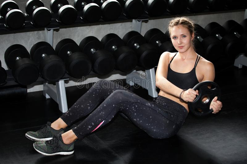 young fitness sport girl doing abdominal exercises with weight barbell plate in gym.woman in sportswear workout sit ups strengthen stock photo