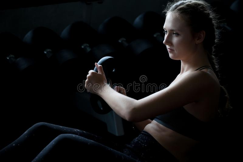 Young fitness sport girl doing abdominal exercises with weight barbell plate in gym.woman in sportswear workout sit ups strengthen. Pumping up the muscles on royalty free stock images