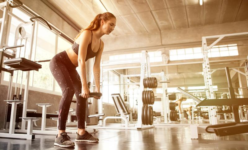 young fitness sport girl doing exercise squat with weight barbell plate in gym.woman in sportswear workout strengthen pumping up royalty free stock photo