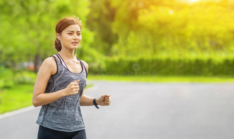 Young fitness sport woman running on the road in the morning, Young fitness sportswoman runner running on tropical park trail. Peo stock photography